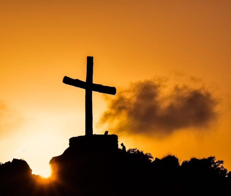 A cross with a rising sun behind it.